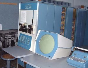 An original PDP-1 computer - a circular monitor next to a large input console